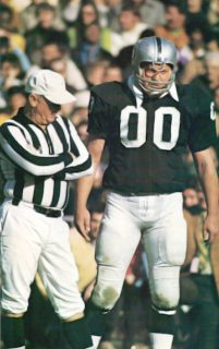 Jim Otto of the Oakland Raiders on the sideline with referee.